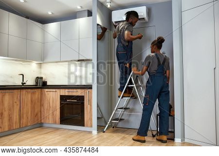 Young Handsome Handyman Standing On Ladder, Checking Air Conditioners Remote Controller. Pretty Fema