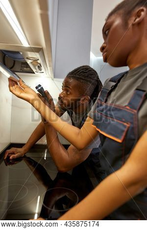 Portrait Of Diverse Couple Of Skilled Electricians. Young African American Man And Woman In Kitchen,
