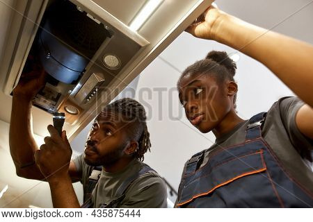 Young Unexperienced Electricians Female Apprentice Watching Professional Work Of Her Mentor. African
