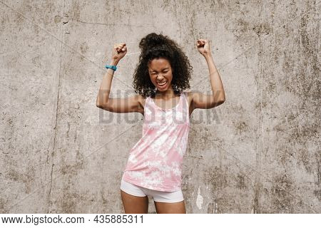 Young black sportswoman screaming while making winner gesture by concrete wall