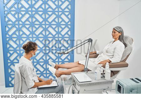 Attentive Nail Master Consulting Her Visitor Before Procedure