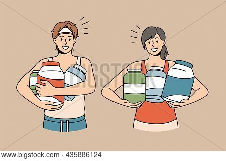 Dietary Supplement And Sport Concept. Young Smiling Couple In Sportswear Standing Holding Jars With
