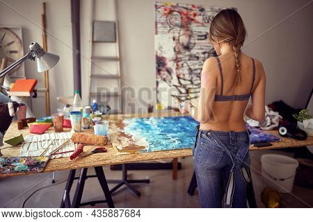Shot from of a back of a young sexy and attractive female artist in a bra who is standing over her new painting in a relaxed atmosphere in her studio and observing. Art, painting, studio