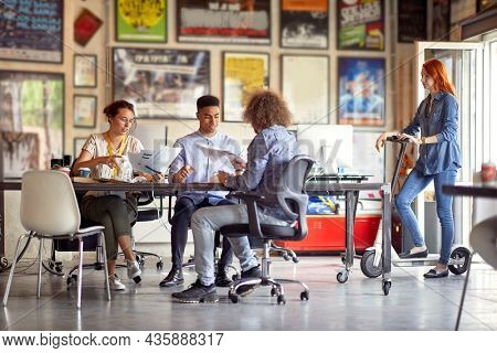 multiethnic group of colleagues working together, smiling, siting at the desk with their colleague standing on electric scooter beside, observing