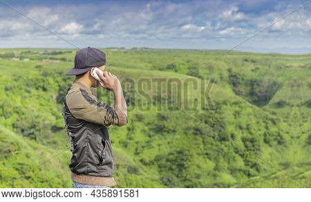 Young Man Calling By Cell Phone, Young Man In Field Calling By Cell Phone, Young Man Calling By Phon