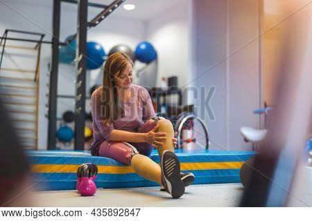 Young woman with prosthetic legs exercising at physiotherapy center