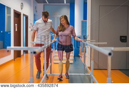 Young woman walking with prosthetic limbs being assisted by male physiotherapist