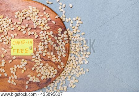 Top View On A Wooden Surface On A Gray Background With Scattered Nuts Of Siberian Cedar. The Inscrip