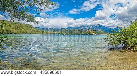 View Of Bled Castle And Pilgrimage Church With The Alps In The Background In Slovenia During The Day