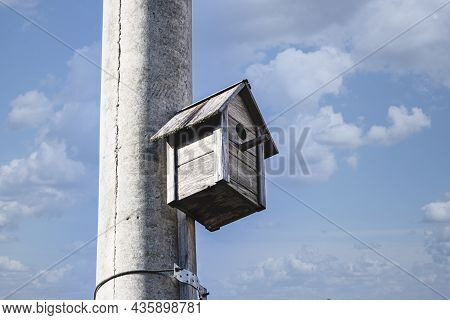 Birdhouse For Birds On A Concrete Pole In The City Center Against The Blue Sky. Taking Care Of Birds