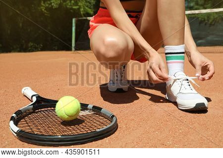 Woman Tying Shoelaces And Tennis Racket With Ball On Court, Closeup