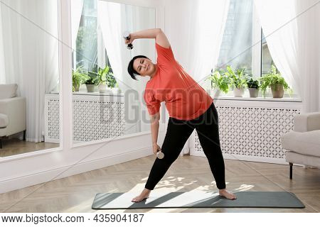Overweight Mature Woman Doing Exercise With Dumbbells At Home