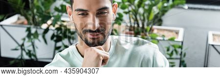 Young Muslim Businessman In Wireless Earphones In Office, Banner