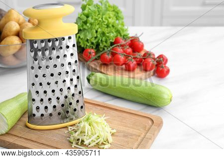 Grater And Fresh Vegetables On White Table In Kitchen. Space For Text