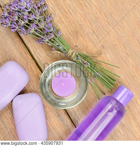 Lavender Flowers, Soap, Scented Candle And Shampoo On A Wooden Background. Beauty And Spa Products.