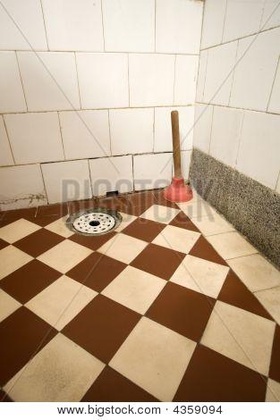 Old Toiler rubber plunger on tile floor poster