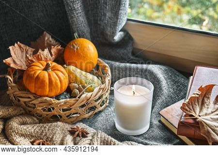 Cozy Autumn Still Life With Pumpkins, Knitted Woolen Sweater, Books And Candle On The Windowsill. Au