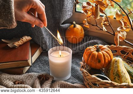 Hand With Burning Match Lighting A Candle On The Windowsill With Cozy Autumn Still Life With Pumpkin