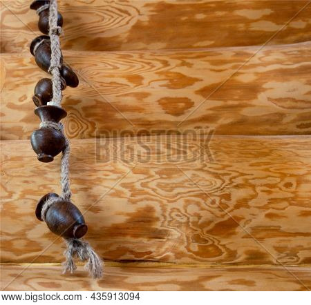 A Beautiful Decoration In A Rustic Wooden Log House, Clay Pots Are Hanging On A Rope. Copy Space For