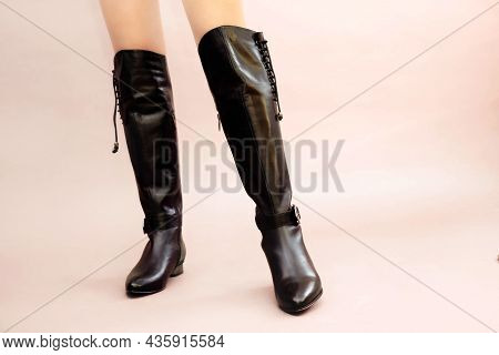Caucasian Female Legs In Sexy Black Leather High Long Boots Jackboots On Light Pink Beige Background