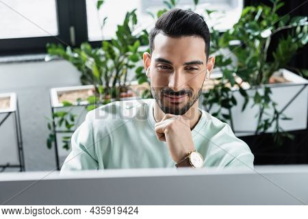 Smiling Arabian Businessman In Wireless Earphones Looking At Blurred Computer Monitor In Office