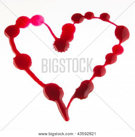 Drops of red ink in the form of heart.