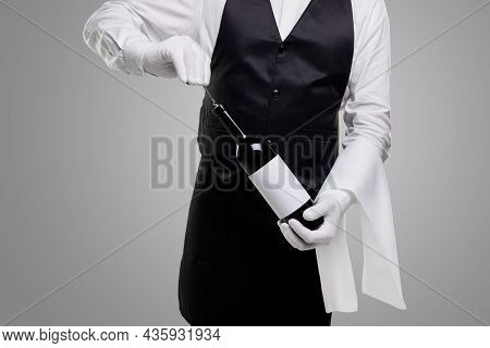 Crop Unrecognizable Stylish Waiter In Gloves With Corkscrew Opening Bottle Of Red Wine On Gray Backg