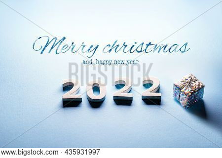 Merry Christmas Theme. Happy New Year 2022. Minimal Christmas Card On A Blue Background With A Gift.