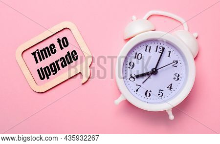 On A Delicate Pink Background, A White Alarm Clock And A Wooden Frame With The Text Time To Upgrade