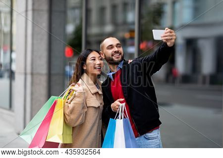 Cheerful Multiracial Couple With Shopper Bags Taking Selfie On Smartphone In Front Of Big Supermarke