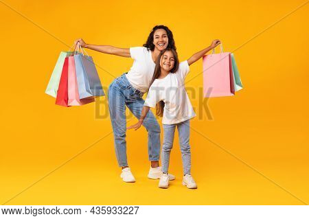 Arab Mother And Daughter Shopping Holding Shopper Bags, Yellow Background