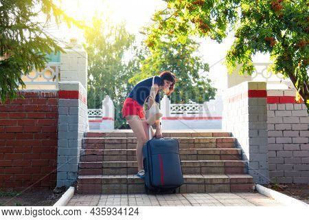 A Woman With Heavy Suitcase Hardly Climbs The Stairs Of Railway Station.