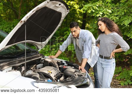 Frustrated Middle-eastern Couple Having Broken Car While Countryside Trip