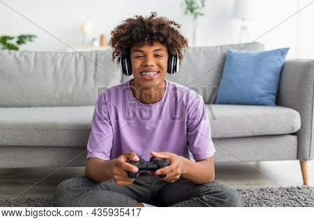 Portrait Of Cool Black Teen Gamer With Controller Playing Online Video Games, Wearing Headphones At