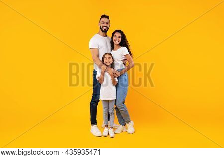 Full-length Shot Of Middle-eastern Family Hugging Standing On Yellow Background