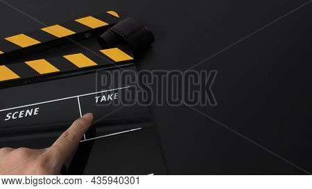 Yellow And Black Clapper Board Or Movie Slate On Black Background And Hand Pointing. It Use In Movie