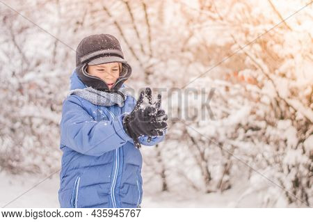 The Child Plays Snowballs Against The Background Of A Snow Forest.