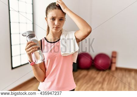 Young brunette teenager wearing sportswear holding water bottle confuse and wondering about question. uncertain with doubt, thinking with hand on head. pensive concept.