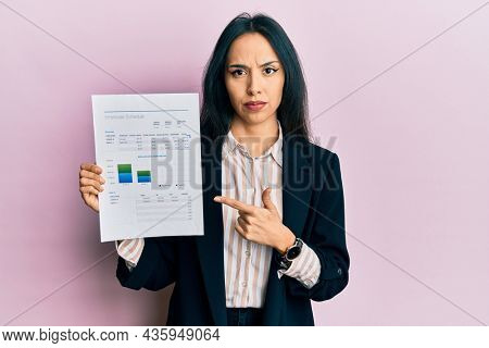 Young hispanic girl wearing business jacket holding document skeptic and nervous, frowning upset because of problem. negative person.