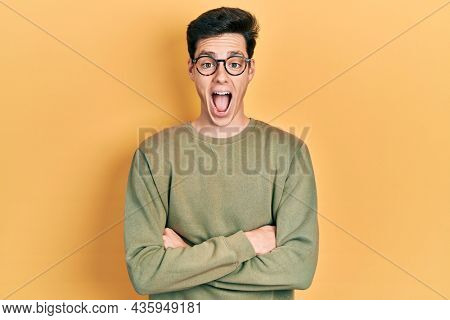 Young hispanic man with arms crossed gesture celebrating crazy and amazed for success with open eyes screaming excited.
