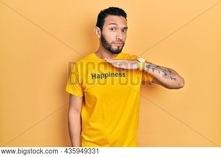 Hispanic man with beard wearing t shirt with happiness word message cutting throat with hand as knife, threaten aggression with furious violence
