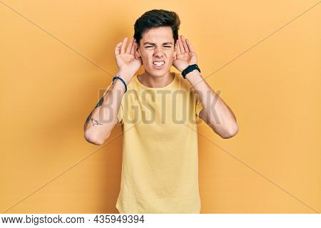 Young hispanic man wearing casual yellow t shirt trying to hear both hands on ear gesture, curious for gossip. hearing problem, deaf