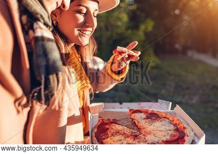 Loving Couple Having Pepperoni Pizza In Fall Park. Woman And Man Enjoy Tasty Food Outdoors. Eating H