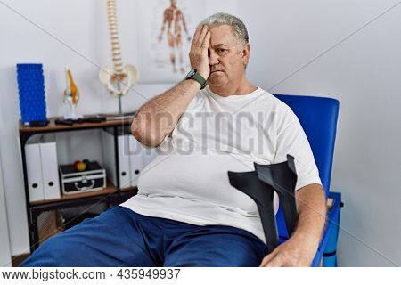 Senior caucasian man at physiotherapy clinic holding crutches yawning tired covering half face, eye and mouth with hand. face hurts in pain.