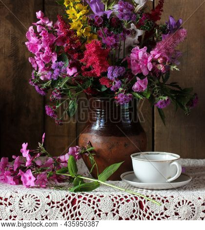 Lush Bouquet Of Garden Flowers Snapdragon And Phlox Flowers In A Clay Jug And A White Cup On The Tab