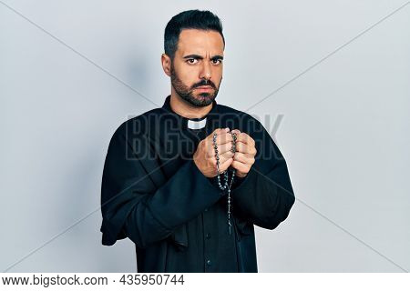 Handsome hispanic priest man with beard praying holding catholic rosary skeptic and nervous, frowning upset because of problem. negative person.