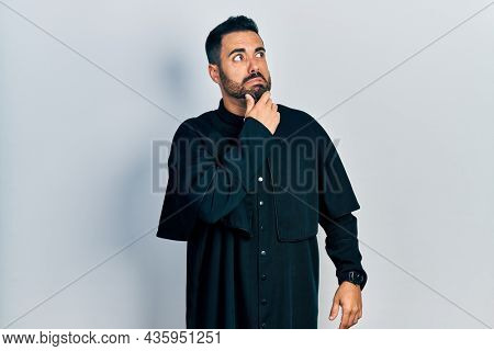Handsome hispanic man with beard wearing catholic priest robe thinking worried about a question, concerned and nervous with hand on chin
