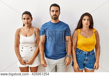 Group of young hispanic people standing over isolated background relaxed with serious expression on face. natural looking at the camera.