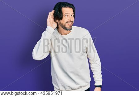 Middle age caucasian man wearing casual clothes smiling with hand over ear listening an hearing to rumor or gossip. deafness concept.