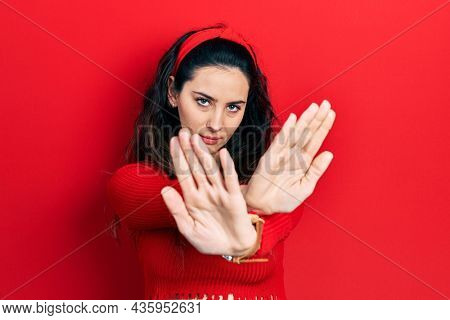 Young hispanic woman wearing casual clothes rejection expression crossing arms doing negative sign, angry face